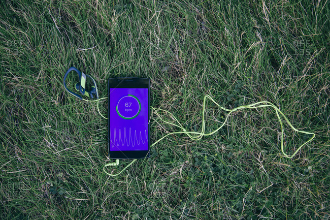 Top view of smartphone with app showing heartbeat lying on green grass with headphones