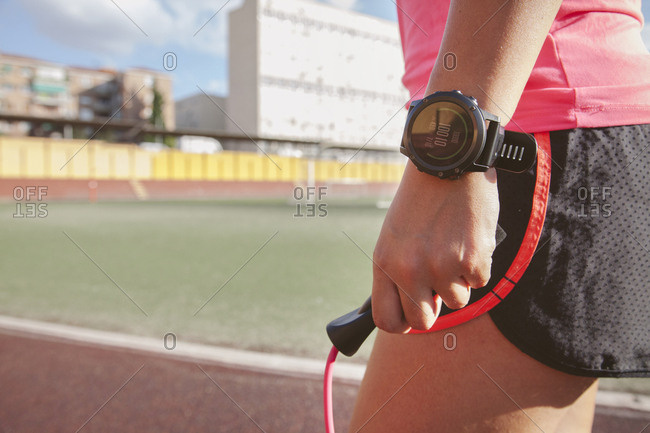 Crop shot of woman in sportswear and smart watch holding skipping rope and training on stadium