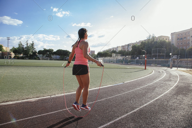 View of woman in bright sunlight training on racetrack and jumping rope under blue sky