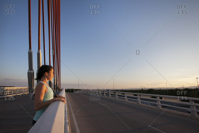 Happy casual woman leaning on fence of bridge and smiling at camera in bright sunlight