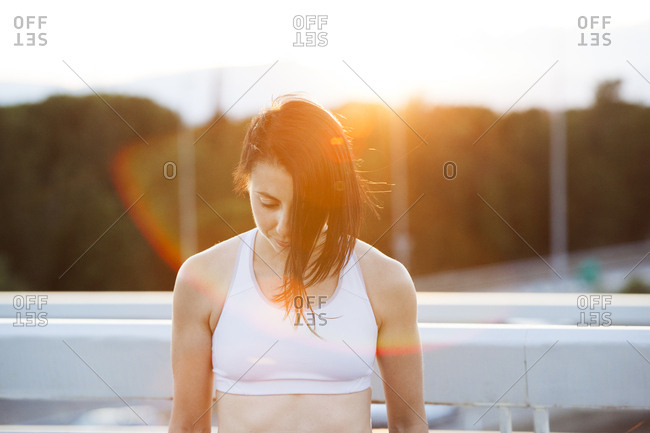 Confident sportive woman with trendy hairstyle looking forward with determination in bright sunshine