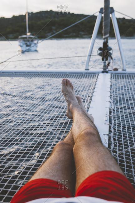 Man lying in boat sailing on lake