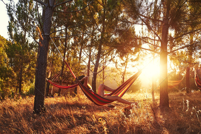 Woman lying in hammock at sunny woods