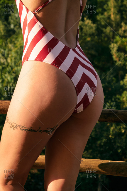 Unrecognizable tanned female ass with tattoo inscription in red with white stripped swimsuit on blurred background with wooden fence and thick forest