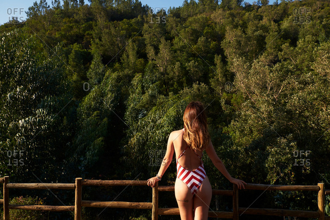 Unrecognizable woman with brown hair wearing red and whiter stripped swimwear standing on observation point and looking to thick green forest