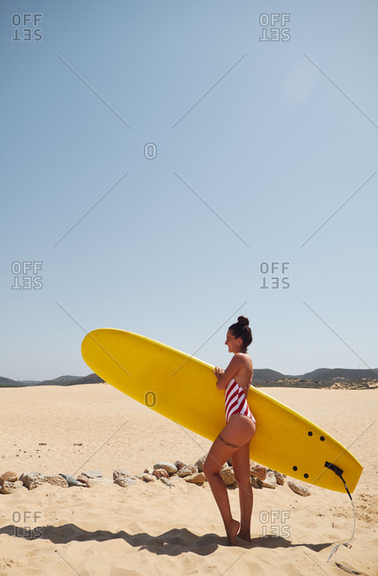 Pretty woman with surfboard on beach