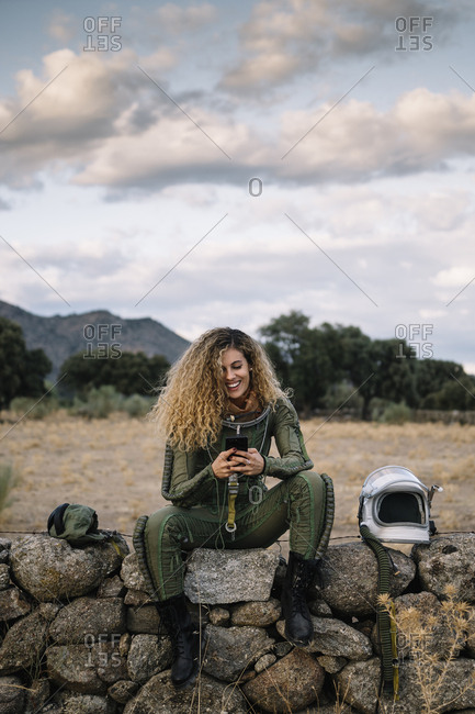 Beautiful female astronaut with mobile phone.