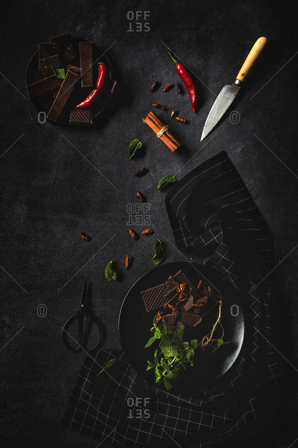 Chocolate with red chili peppers, mint and raspberries on dark background. Flat lay