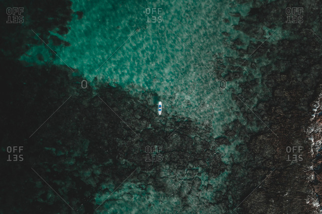 From above drone view of small boat sailing in transparent green ocean