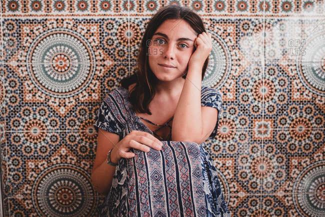 Young brunette woman in summer dress sitting near patterned wall and looking at camera