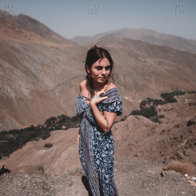 Side view of young attractive brunette woman in summer floor length dress standing near dangerous steep cliff and looking aside on background of mountain