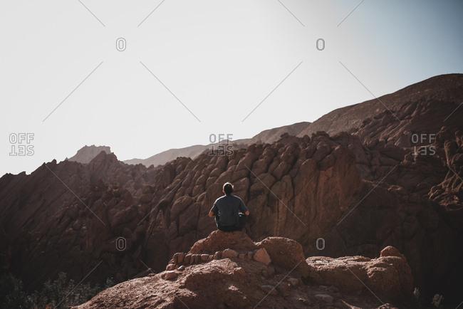 Back view of man in T-shirt and trousers on steep cliff and looking at rocky mountain on background of clear cloudless sky