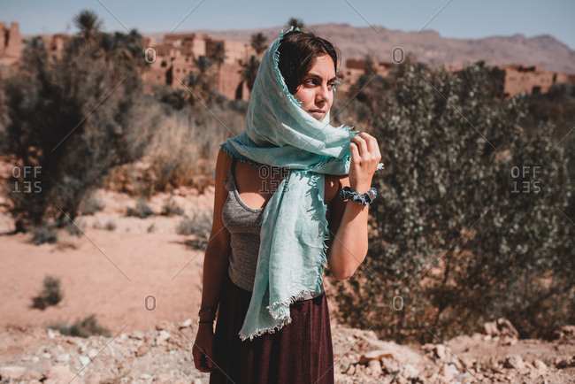 Young attractive woman with dark hair and kerchief on head standing in desert on background of sand and trees and looking at camera
