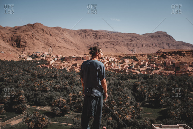 Back view of man in T-shirt and trousers standing on steep cliff and looking at rocky mountain on background of clear cloudless sky
