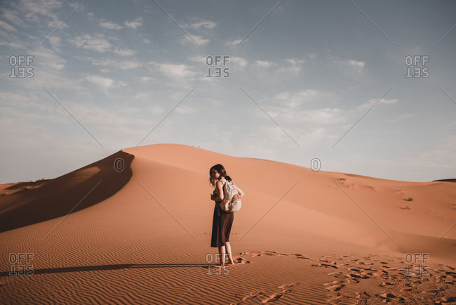 Back view of young woman with dark hair and backpack walking on sands of desert in Morocco on background of blue sky