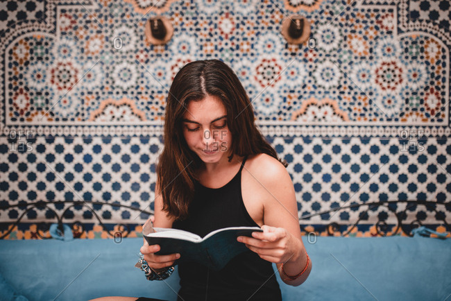 Young attractive brunette woman in black dress sitting on blue couch and reading book in room on background of patterned wallpaper