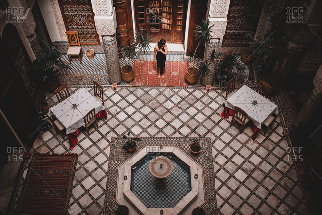 From above view of woman in black dress entering spacious hall of hotel decorated with fountain in middle