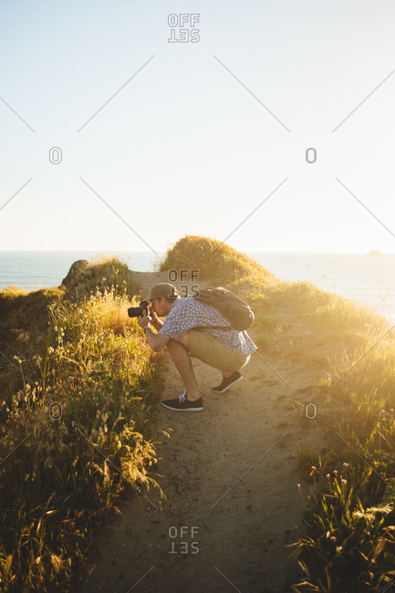 Side view of young guy using professional photo camera to take photos of amazing nature during sunset on beach in California