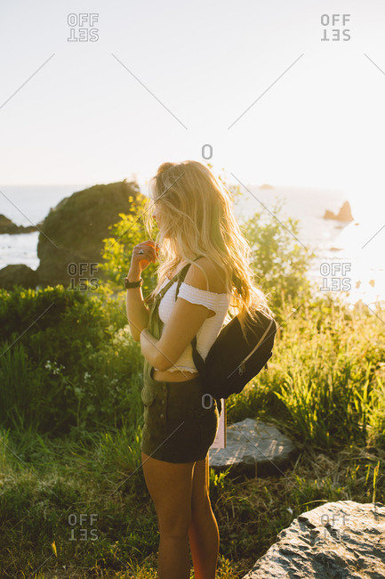 Side view of unrecognizable female in casual outfit standing near sea during amazing sunset on beach in California