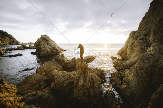 Unrecognizable person standing on cliff near sea
