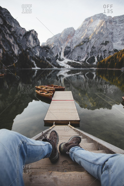 Legs of anonymous man lying on steps near pier and calm surface of Pragser Wildsee in Dolomites, Italy