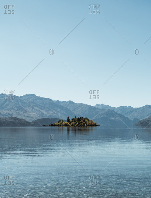 Magnificent view of calm Lake Wanaka and majestic mountain ridge in New Zealand