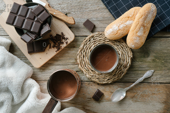Top view of a hot chocolate cup, a cooper pot with hot chocolate and a cutting board with chocolate chunks