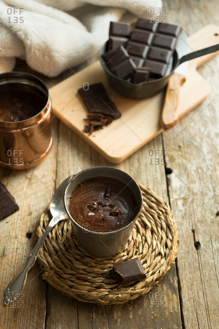 Cup of hot chocolate with chocolate chunks topping on a wood surface