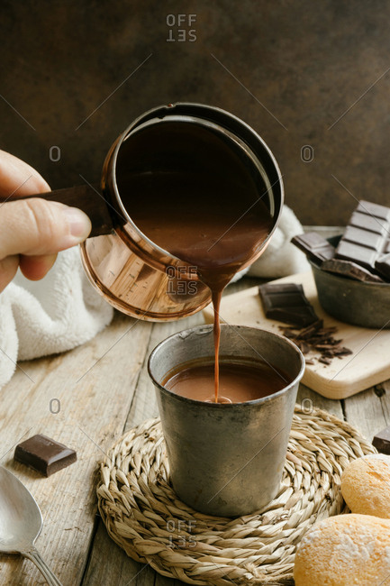 Pouring hot chocolate from a cooper pot into a metal cup