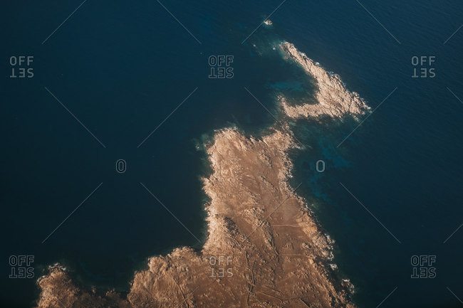 From above view of rock seashore with dark blue sea in Mykonos