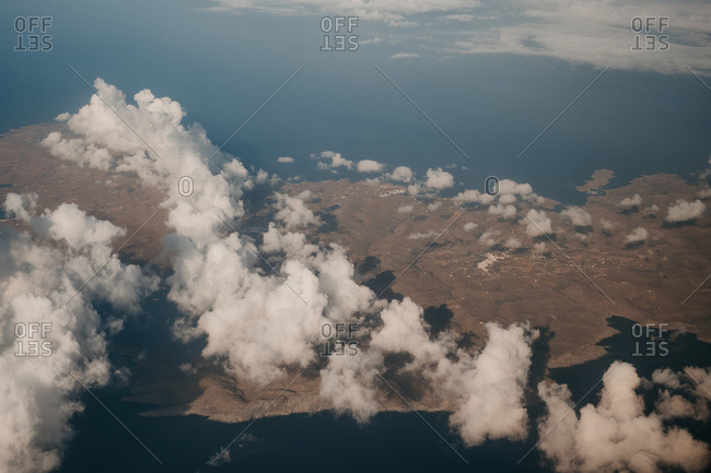 From above view of white clouds on heaven on island and sea background in Mykonos