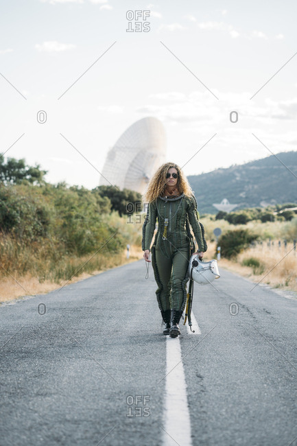 Beautiful woman walking along the road dressed as an astronaut.
