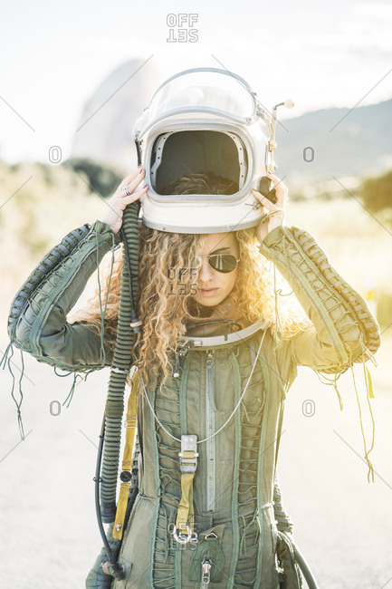 Beautiful woman putting the helmet dressed as an astronaut.