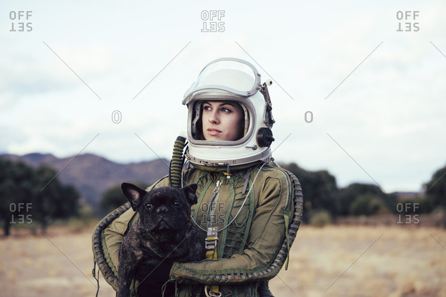 Girl wearing old space helmet holding a dog