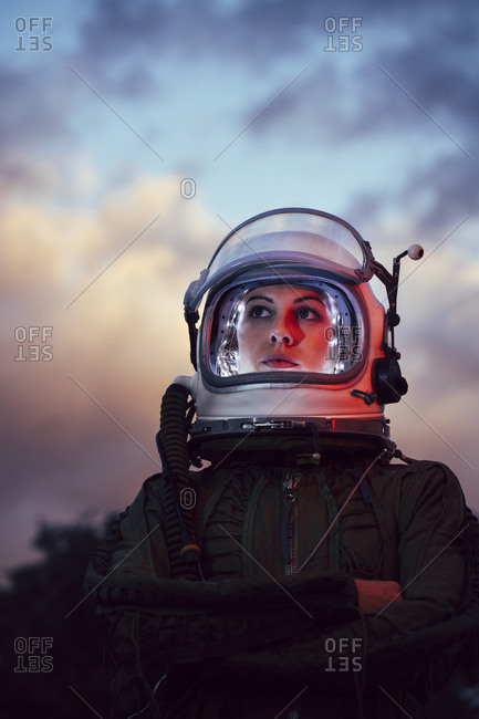 Girl wearing old space helmet at sunset