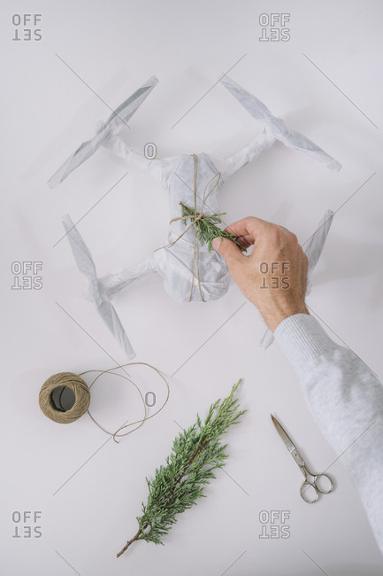 Man packing to Christmas gift, is a drone.