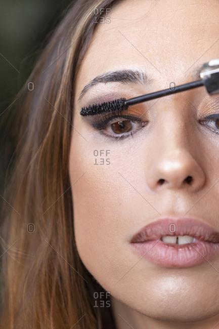 Crop hands applying mascara on model