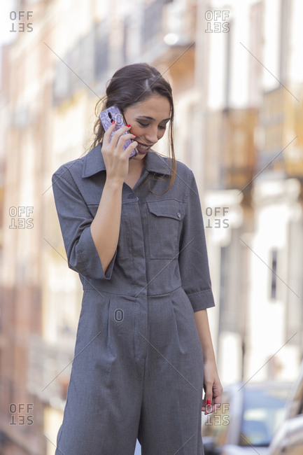 Cheerful woman speaking on smartphone on street
