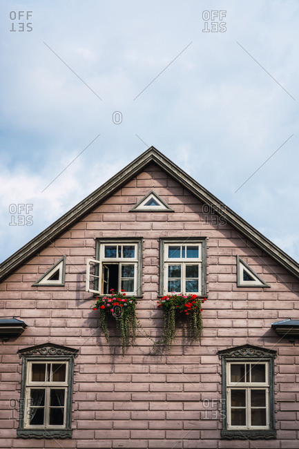 Beautiful flowers and lovely windows located on brick wall of countryside house on background of blue cloudy sky