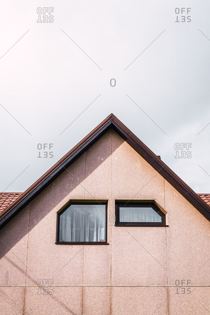 Two windows of unusual shape located on light wall under roof of modern countryside house against cloudy sky