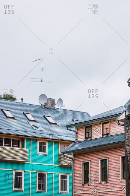Two building with satellite dishes on roof standing on street of small town against gray sky