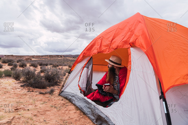 Man with mug into a tent in Grand Canyon