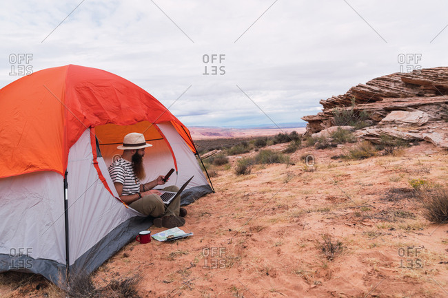 Attractive bearded guy using laptop and looking away while sitting near tent and map with compass