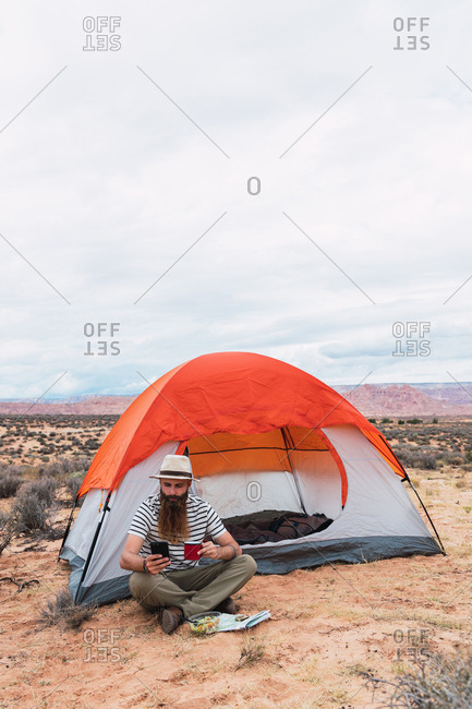 Bearded guy in casual outfit holding mug of hot beverage, salad and modern smartphone while sitting near tent and looking away in beautiful nature