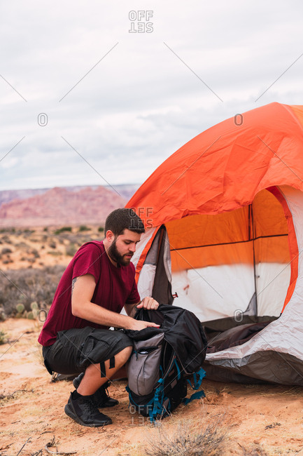 Side view of handsome guy in casual outfit packing backpack while sitting on ground near tent on camping area in desert