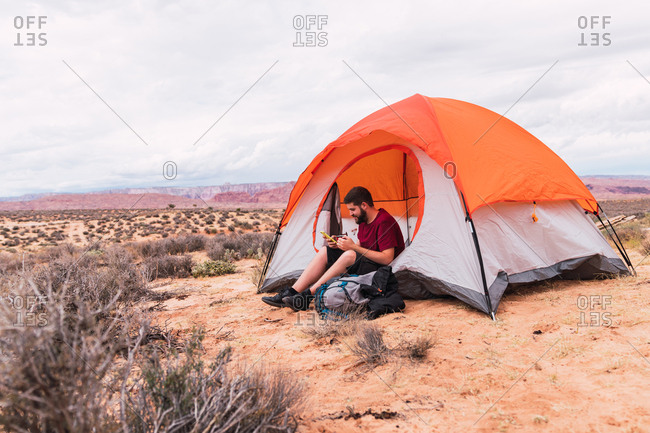 Bearded guy in casual outfit holding mug of hot beverage and modern smartphone while sitting near tent and looking away in beautiful nature