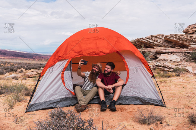 Travelers taking selfie with smartphone near tent
