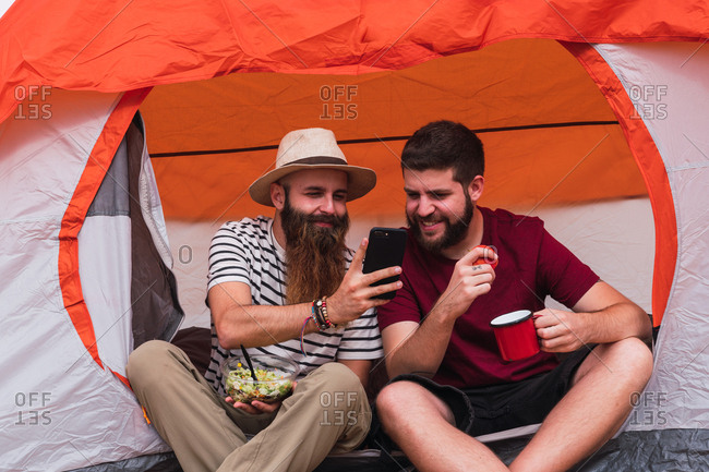 Travelers eating and near tent with smartphone