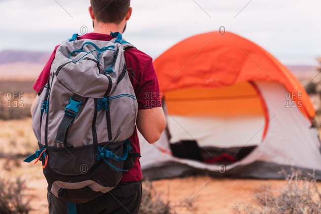 Back view of man with backpack walking towards modern tent while camping in desert