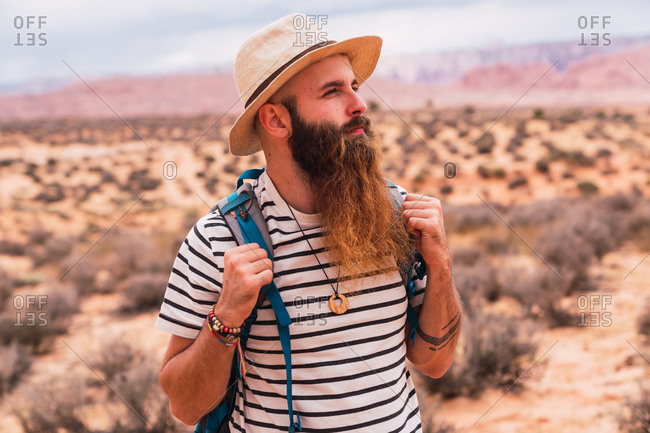 Handsome bearded guy with backpack looking away while standing on blurred background of amazing desert